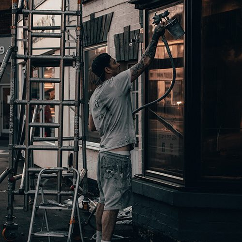 man painting exterior of building