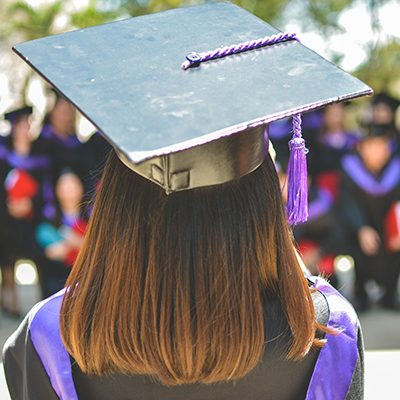 female with cap and gown looking at class