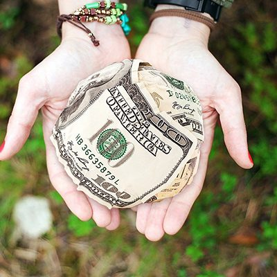 hands with a ball of money