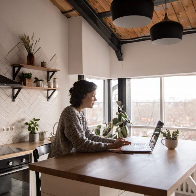 woman looking at laptop in her kitchen