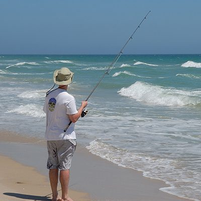 fisherman on beach with waves